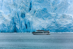 Boat traveling past large glacier shows how enormous the ice formation is Stock Images