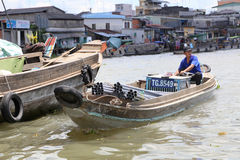 A boat travels through a floating market on the Mekong river in Viet Nam Stock Photo