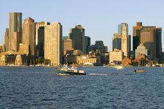 Boat travels in front of Boston Harbor and the Boston skyline at sunrise as seen from South Boston, Massachusetts, New England Royalty Free Stock Photos
