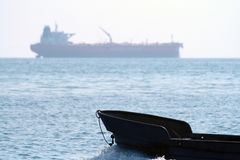 Boat and trawler on the horizon in the sea Stock Photography