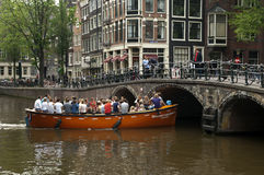 Boat trip on the historic canals of Amsterdam. On the canal Oudezijdsvoorburgwal, sails a brightly colored orange boat, named schavuit van Oranje, rascal of royalty free stock images
