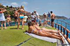 Boat trip near Antalya coast, tourists take sunbathe or photographed. Antalya, Turkey - 28 august, 2014: Tourists on board leisure boat trip, passengers get stock image