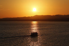 Boat trip during sunset over the sea and Mounties Stock Image
