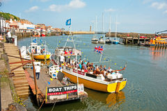 Boat trips in Whitby. Inexpensive boat trips from the harbor around the bay: entertainment for holidaymakers at Whitby, East Yorkshire Stock Images