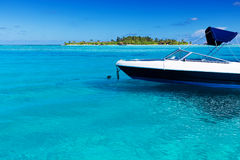 Boat in tropical lagoon with island in background Royalty Free Stock Images