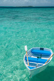 Boat on tropical sea. A row boat floats on the clear cyan sea in the Maldives, with island on distant horizon Stock Photos