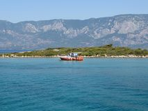 Boat with Turkish flag near green rocky island in the Aegean sea. Picturesque Mediterranean landscape with green islands and turquoisу water. Sea trip concept royalty free stock image