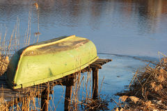 Boat turned upside down lying on small fishing pier at a lake sh Stock Photo
