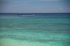 Boat at turquoise reef within sea. Crystal clear water royalty free stock photos