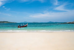 Boat on turquoise sea. Beautiful panoramic view from sandy beach on longtail boat tied on turquoise sea shore in sunny summer day isolated over blue sky Stock Photo