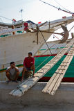 Boat and two workers of the Sunda Kelapa harbour Jakarta, Indone Stock Photography