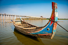 Boat by ubein bridge. A swan boat on the taungthaman lake by The 1,5 km long teak bridge at sunset in Amarapura, central Myanmar Stock Photo