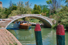 Boat Under the bridge. A beautiful wooden boat going under a low bridge on the canal on the island of Torcello. This island is in the lagoon of Venice Stock Images