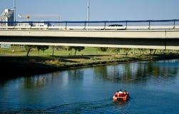 Boat under the bridge. Three people on a red pedal boat under a bridge drifting in the Yarkon river,Tel Aviv, Israel Stock Photo