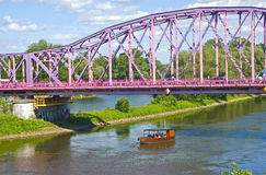 Boat under the pink bridge. Boat and the pink bridge over The Oder River in Glogow, Poland Stock Image