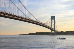 A boat under Verrazano-Narrows Bridge. The largest and longest bridge in New York City royalty free stock photos