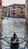 Boat on a Venetian Canal. Venice,Italy- February 18, 2012: A lonely man in a boat paddeling on a Venetian Canal in the morning during the Venice Carnival days Stock Images