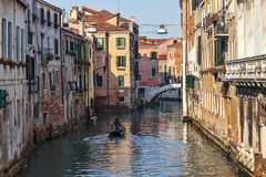 Boat on a Venetian Canal. Venice,Italy- February 18, 2012: A lonely man in a boat paddling on a Venetian Canal in the morning during the Venice Carnival days Stock Image