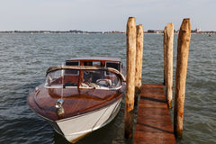 Boat in Venice. Motorboat docked near the wooden poles in Venice Stock Photography