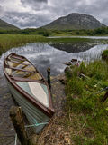 Boat waiting for passengers. A boat tied to a rope at the shore of a beautiful lake surrounded by mountains Stock Photo