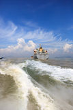Boat wake and cargo ship Royalty Free Stock Photo
