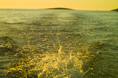 Boat wake foam water from propeller. At sunset Royalty Free Stock Photo