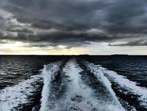 Boat Wake with Moody Sky. Boat wake on a dark sea with a moody sky near dusk royalty free stock photos