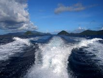 Boat wake waves blue sea blue sky horizon. A boat cruising in the Caribbean Sea creates a symmetrical wake rippling out towards distant islands on the horizon Stock Photo