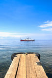 Boat on water with dock (lake Baikal). A boat on the water of lake Baikal with dock in the foreground Royalty Free Stock Photo