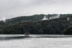 Boat on the water with a forest. On the background and some mist Stock Photos