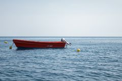 Boat on water with red vivid color. Red wooden boat on blue water with motorboat. rescue boat on the sea royalty free stock photography