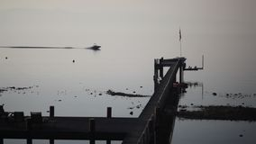 Boat with water skier driving by a pier during sunrise stock video