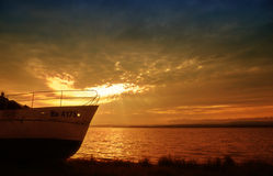 Boat on water with sunset. Pleasure boat on water with an orange sunset in the background Royalty Free Stock Photo