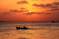 Boat on water at sunset. Silhouette of a small, open boat on water with a golden sunset in the background Stock Photo