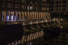 A boat in the water surrounded by the reflections of the nearby buildings at night. A boat in the water surrounded by the reflections of the nearby buildings at stock photos