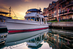 Boat and waterfront condominiums reflecting in the water at suns Royalty Free Stock Image