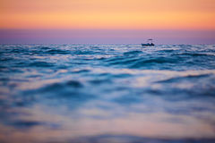 Boat on waves at sunset Royalty Free Stock Photo