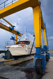Boat wheel crane elevating motorboat to yearly paint. Task Stock Photos