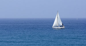 Boat with white sails stock photo