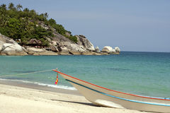 A boat at the white sand beach of the tropical blue sea. Daytime, Koh Phangan, Thailand. A boat at the white sand beach of the tropical blue sea. Daytime, Haad Stock Images