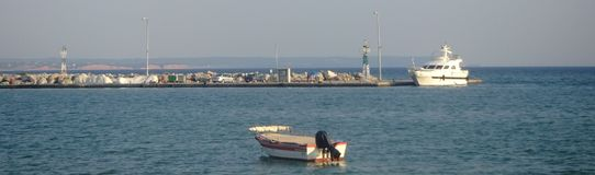 Boat and a white ship in a port. A boat in a blue sea,and a white ship in the distance,in a port in a greek town,Nea Moudania,in a summer day of july Royalty Free Stock Images