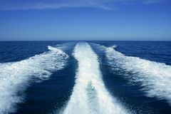 Boat white wake on the blue ocean sea. Fishing speedy boat prop wash, white wake on the blue ocean sea Stock Photos