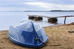 Boat on wild lake beach Stock Photography