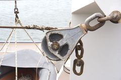 Boat Winch. An old winch shows the wear of time as the metal rope frays stock photo