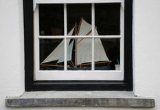 Boat in the window. Interior of a house through the window. On the windowsill a model sailboat Royalty Free Stock Images
