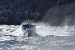 Boat on a windy lake. Splashing waves, lago Maggiore Stock Photo
