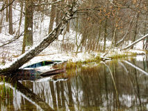 Boat on Winter Lake. Old Boat floating on cold Water of Lake in the middle of Forest Stock Images