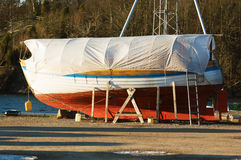 Boat in winter storage. Boats in winter storage covered with tarps and supported by scaffoldings. Winter storage on land protects the boats from the sea ice that Stock Photo