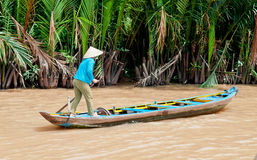 Boat Woman on the Mekong River. A woman in a conical hat paddles a boat in the middle of the Mekong River Royalty Free Stock Photos