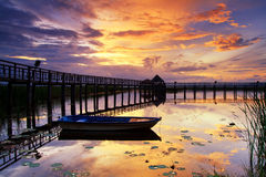 Boat and wooden bridge with  beautiful sky. Stock Photos